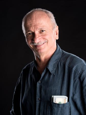 vejez feliz: Viejo hombre afortunado con billetes de un d�lar en el bolsillo sobre un fondo oscuro