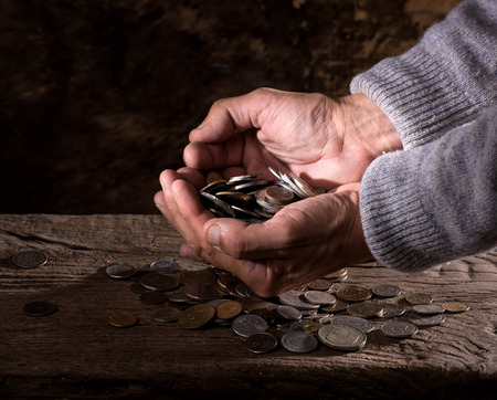 numismatist: Close up of  caucasian old mans hands  and pile of old coins on a wooden background