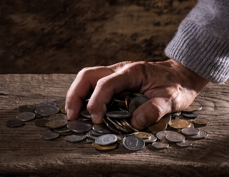 numismatic: Close up of  caucasian old mans hands  and pile of old coins on a wooden background