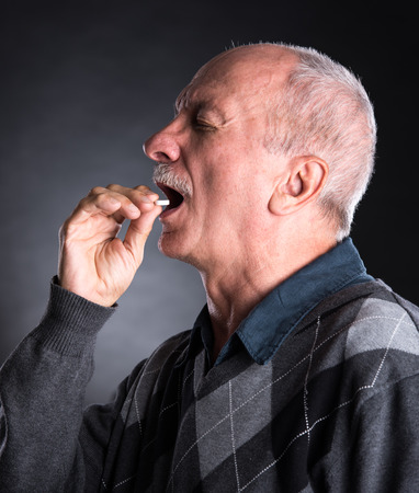 pill: Elderly man wants to take a pill  on a dark background Stock Photo