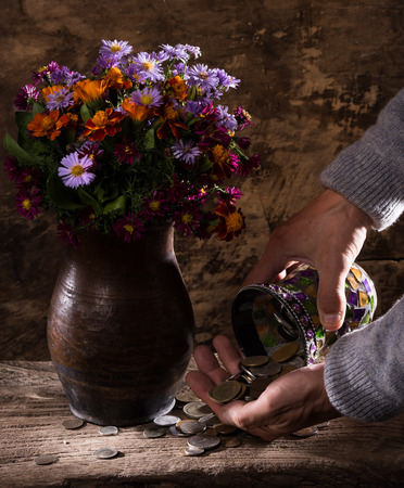 numismatist: Flowers in vase, caucasian old mans hands  and pile of old coins on a wooden background