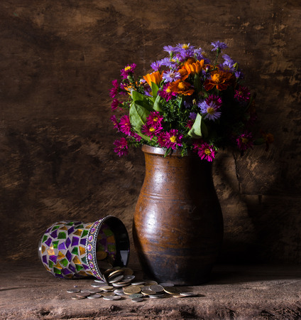 numismatist: Flowers in vase and pile of old coins on a wooden background Stock Photo