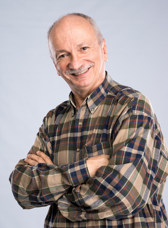 old people: Portrait of a senior smiling man on a light gray background