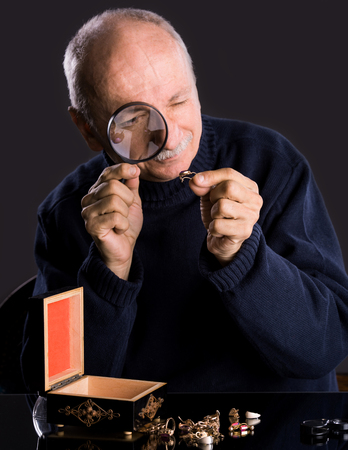 jeweler: Senior jeweler  looking at jewelry through magnifying glass on a dark background
