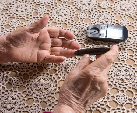 blood sugar level: Close up of old woman with glucometer checking blood sugar level at home Stock Photo