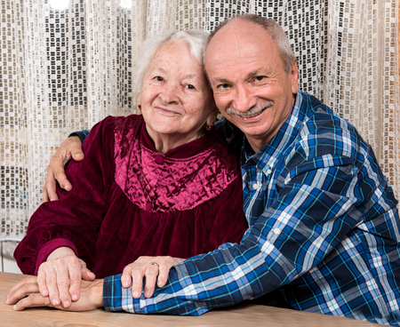 adoring: Smiling old mother with elderly son at home Stock Photo
