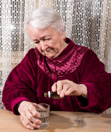 nursing bottle: Old woman dripping medicine at home