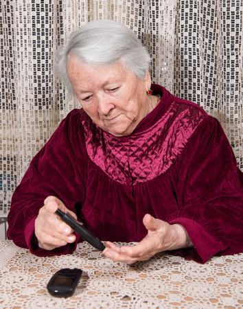 blood sugar level: Old woman with glucometer checking blood sugar level at home Stock Photo