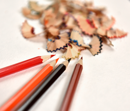 art supplies: Colored pencils and pencil shavings on a light  background