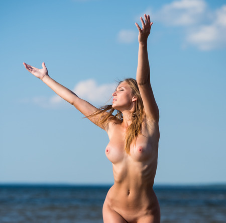 beach breast: Beautiful young naked woman posing on the beach. Enjoying summer time near the sea