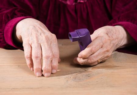 female senior adult: Senior womans hands holding asthma inhaler