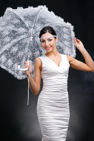Young woman in white dress with white umbrella on a dark background photo