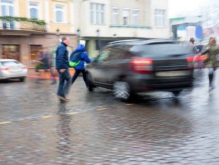 Dangerous city traffic situation with pedestrian and car in motion blur Фото со стока