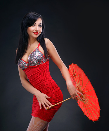 Beautiful young woman in red dress with red chinese umbrella on dark background photo