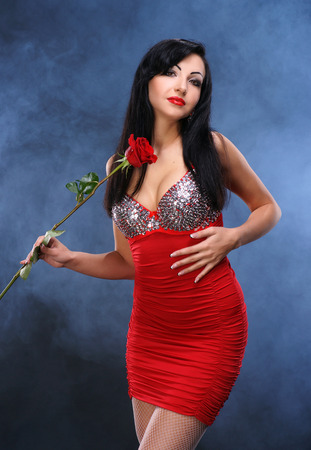 Beautiful young woman with red rose on a smoky background photo