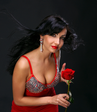 Beautiful young woman with red rose on dark background photo