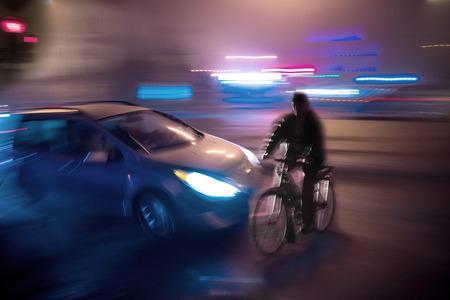 Gevaarlijkste stad verkeerssituatie met een fietser en een auto in de stad 's nachts in motion blur
