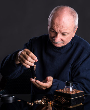 jeweler: Senior jeweler looking at jewelry on a dark background Stock Photo
