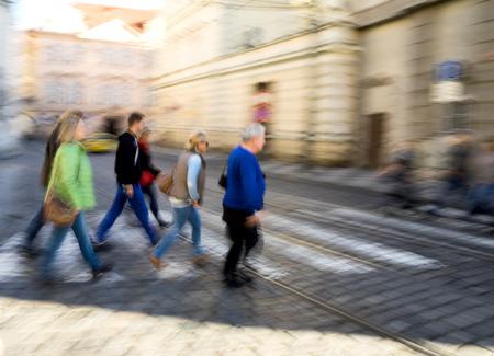 street shot: People crossing the street on the zebra crossing in motion blur. Defocused shot