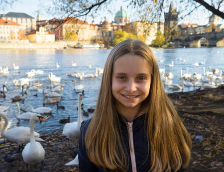 Beautiful girl enjoying sunny day near the river with swans