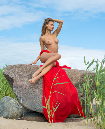 nude nature: Beautiful nude woman in red fabric posing on sea beach