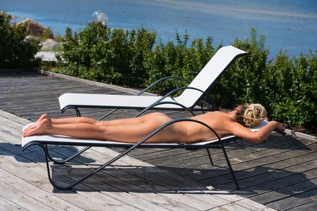 wet breast: Beautiful naked woman sunbathing on sunbed. Enjoying summer time Stock Photo