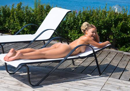 naked youth: Beautiful naked woman sunbathing on sunbed. Enjoying summer time Stock Photo