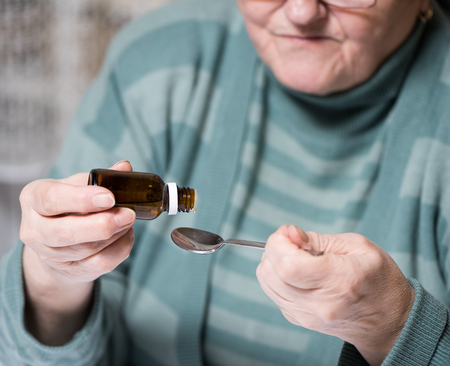 medicated: Close up of mature woman dripping medicated drops into spoon  at home