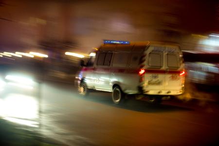 Ambulance in beweging rijden op de weg in de nacht. Opzettelijke bewegingsonscherpte Stockfoto