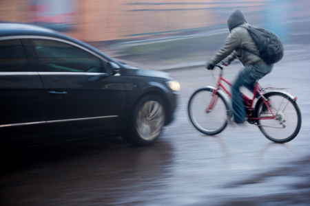 Dangerous city traffic situation with cyclist and car in the city in motion blur