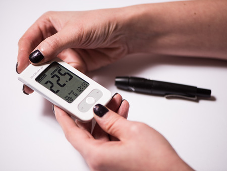 blood sugar level: Close up of young woman checking blood sugar level by glucometer Stock Photo