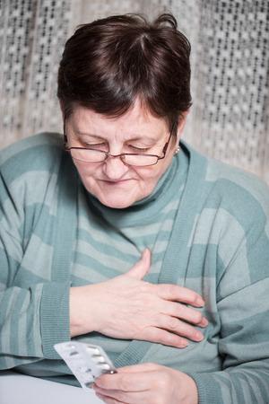 Sad senior woman holding pills at home photo