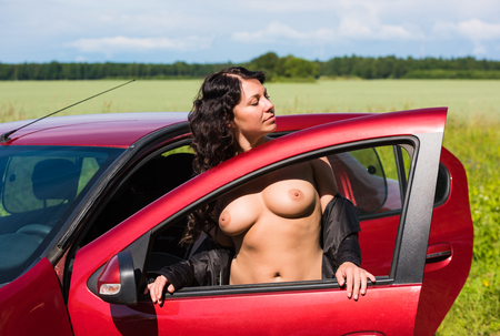 Portrait of beautiful nude young woman posing near the car