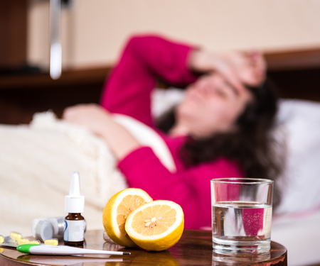 sniffles: Sick woman lying at bed having flu and headache. Medicines on a foreground