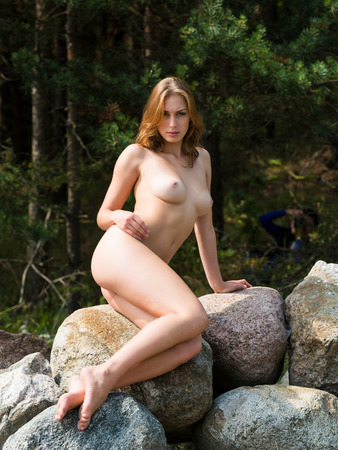 nude nature: Beautiful nude woman posing on stones against nature background