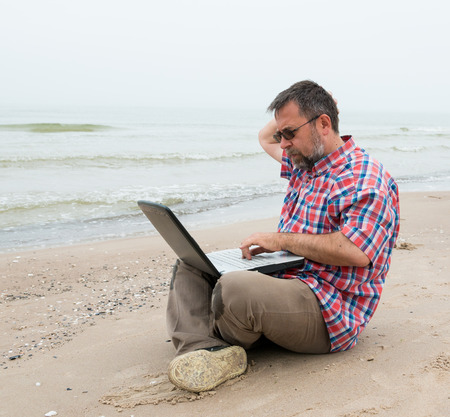 Senior man sitting at the beach with  laptop on a foggy day photo
