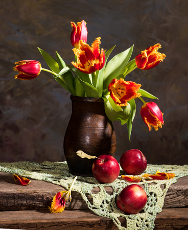 Still life with beautiful tulips and red apples Stock Photo