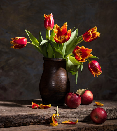 Still life with beautiful tulips and red apples Imagens