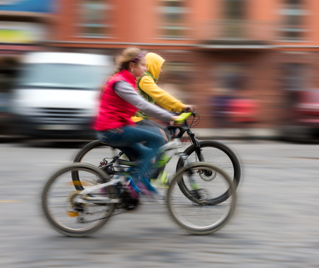 Children riding bicycles on a city street. Intentional motion blur photo