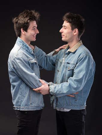 Two handsome young men on a black background. Two brothers