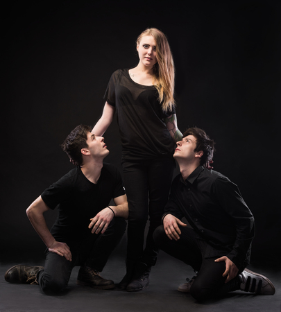 One woman and two men on a black background