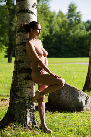 nude nature: Beautiful young naked woman enjoying summer time against nature background Stock Photo