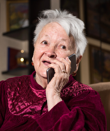 adult 80s: Old woman using smart phone at home Stock Photo