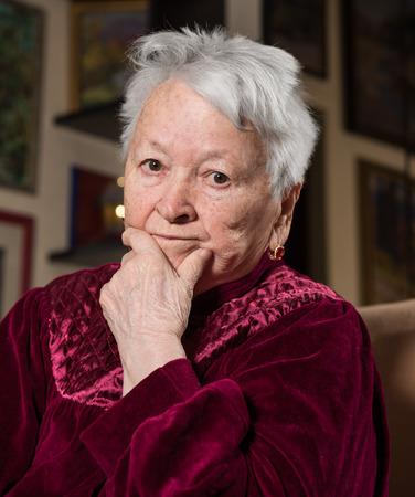 saddened: Portrait of old sad woman at home