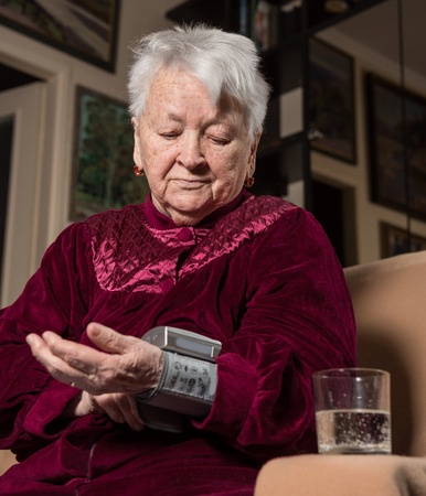 hypotension: Old woman measures arterial pressure at home