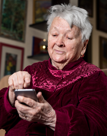 80s adult: Old woman using smart phone at home Stock Photo