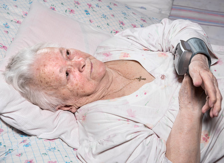 systolic: Old woman measures arterial pressure at home