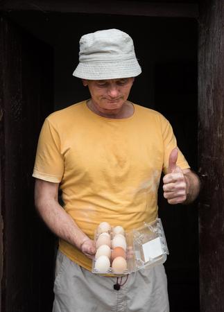 poultry yard: Farmer holding fresh organic eggs. Poultry yard