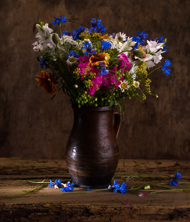 mixed flower bouquet: Beautiful bouquet of bright wildflowers in vase on a wooden background