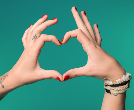 handsign: Female hands in the form of heart on a blue background